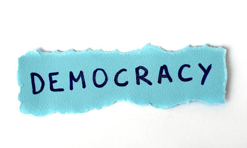 The Word Democracy On Blue Paper Royalty Free Stock Images