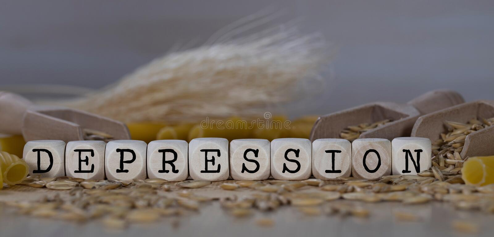 Word DEPRESSION composed of wooden dices. Rye grains in the background. Closeup, allergen, allergy, autoimmune, disorders, celiac, cereals, disease, gluten royalty free stock photos