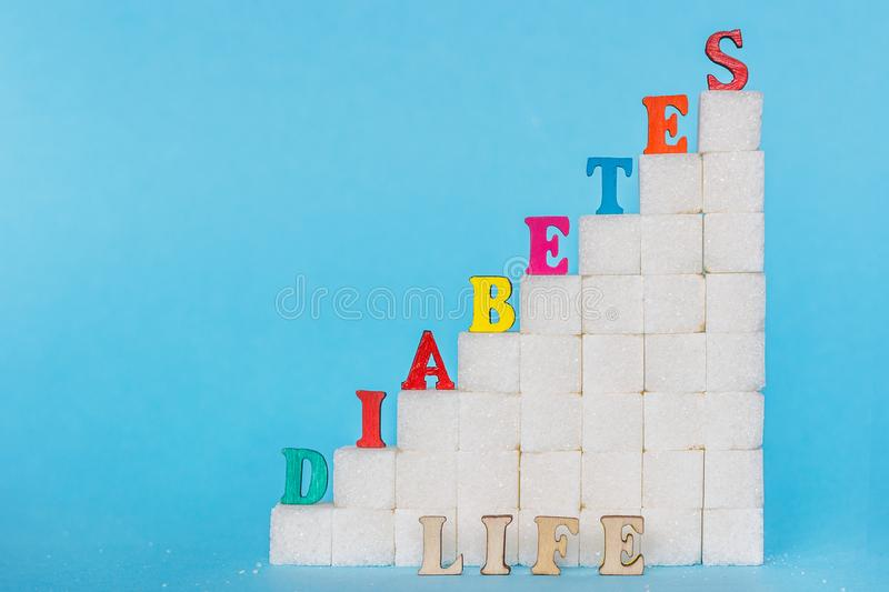 Word diabetes on ladder refined sugar, blue background. Ð¡oncept. Word DIABETES of colored letters and LIFE gray letters on ladder refined sugar, blue royalty free stock photos
