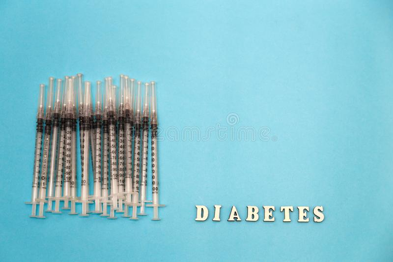 The word diabetes with insulin syringe, on a blue background royalty free stock image