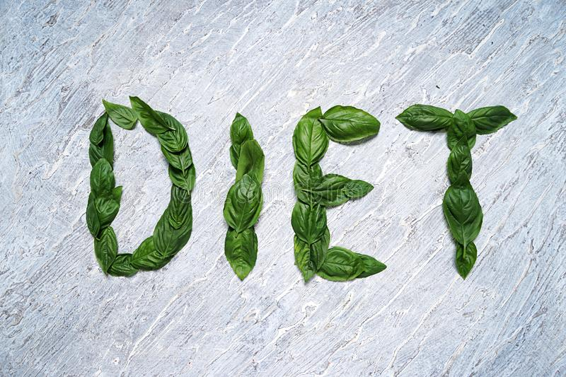 Word DIET made of basil leaves on light background stock images