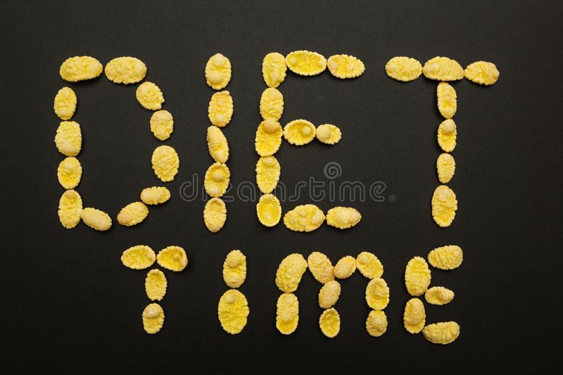 The word `diet time` of cornflakes on a black background. stock image