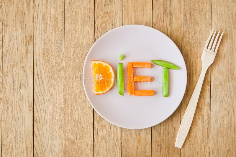 Word Diet, written on a plate of cut fresh fruits stock photos