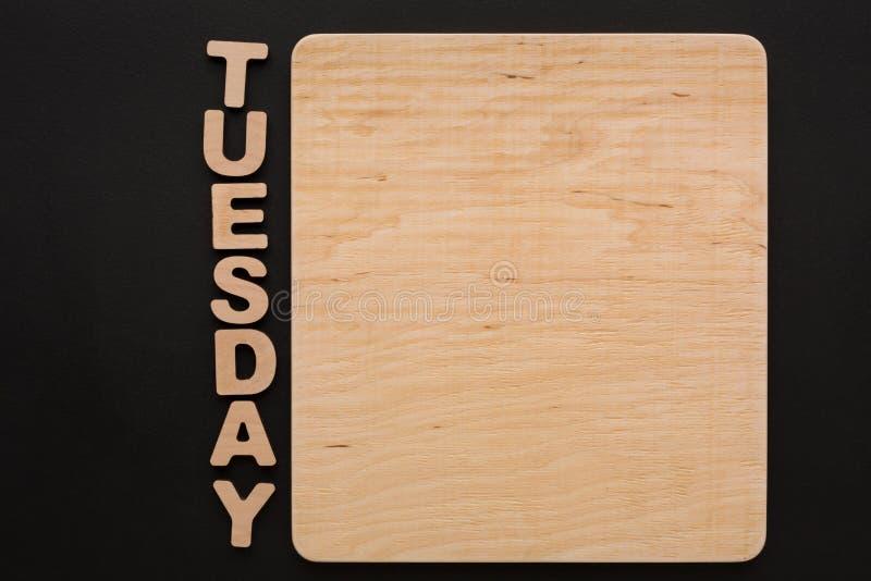 Word Dinsdag met lege houten raad stock foto