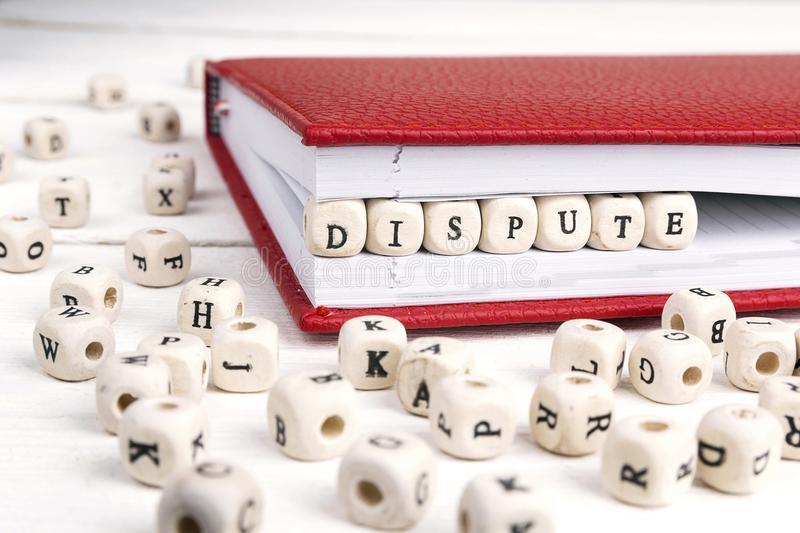 Word Dispute written in wooden blocks in red notebook on white w. Ooden table. Wooden abc royalty free stock photo