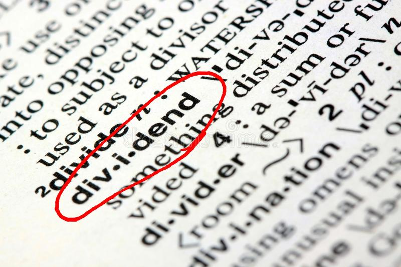 The word dividend in a dictionary. Closeup of the word dividend in the english dictionary stock image