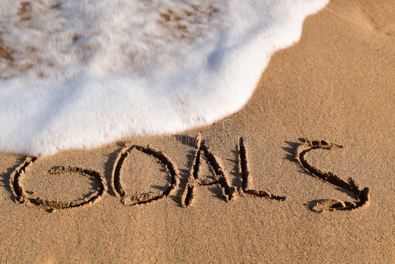 Word doelstellingen in het zand van een strand royalty-vrije stock foto
