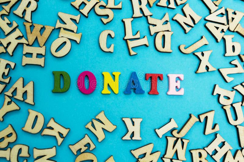 The word `donate` is laid out from multicolored letters on a blue background.  stock photos