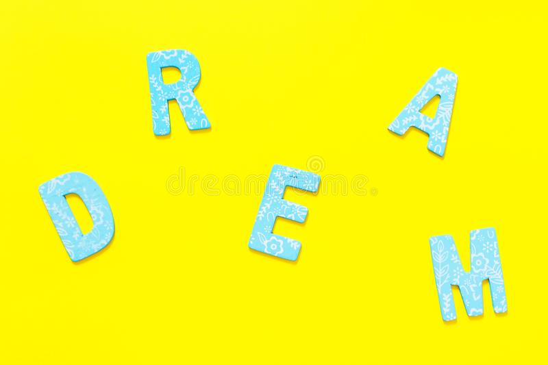 Word DROOM die uit kleine blauwe houten brief op gele backgr wordt gemaakt stock foto