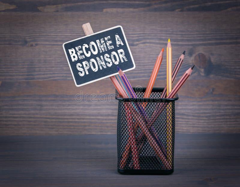 Word een Sponsor Een klein bordkrijt en een kleurpotlood op houten achtergrond stock fotografie