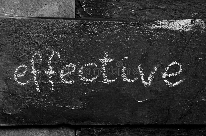 The word EFFECTIVE written with chalk on black stone. The word EFFECTIVE written with chalk on black stone stock photos
