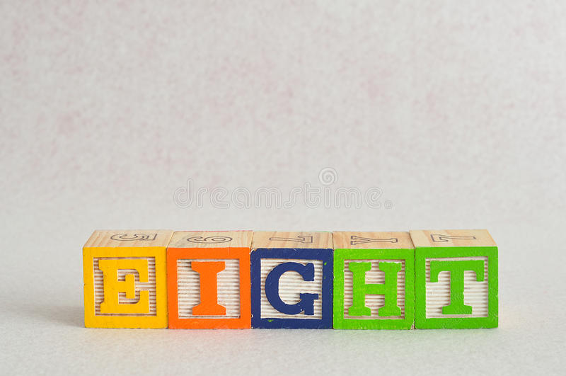 The word eight (8) spelled with colorful alphabet blocks stock images