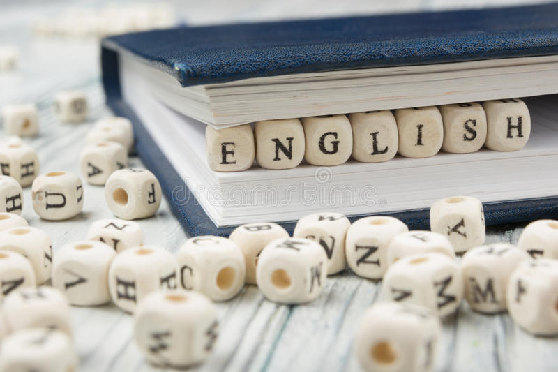 Word english made with block wood letters next to a pile of other letter over wooden table stock photography