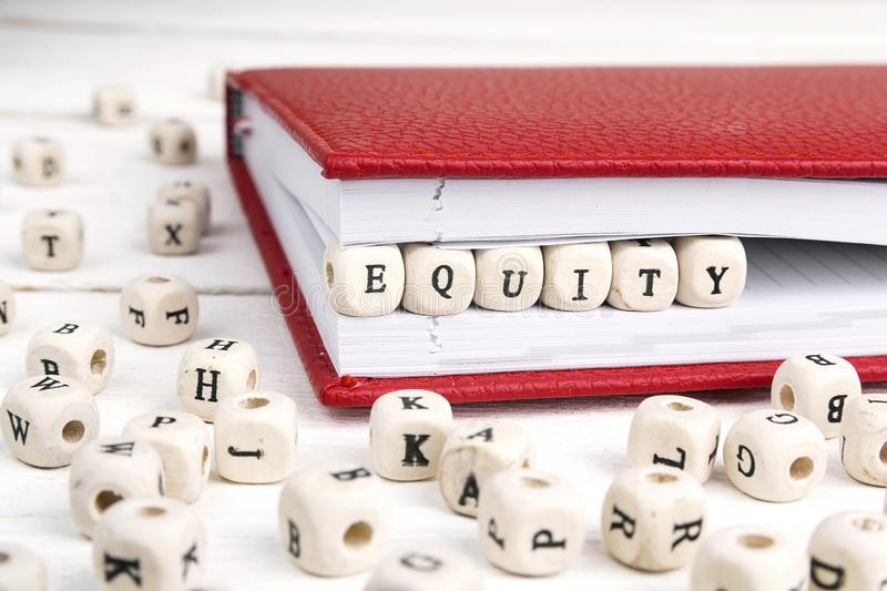 Word Equity written in wooden blocks in notebook on white table. Word Equity written in wooden blocks in red notebook on white wooden table stock images