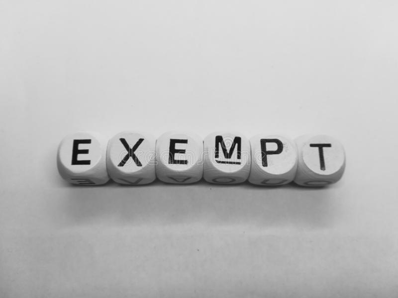 Word exempt spelled in dice. Spelling of word exempt using wooden dice on white background royalty free stock photos