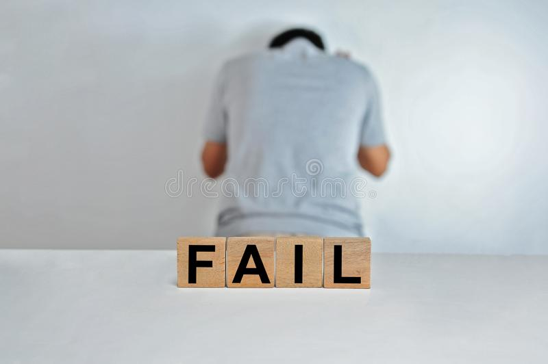 The word fail on wooden cubes, a person doing fail gesture on blur background, light wooden cubes signs, symbols signs. Business office, site content royalty free stock photo