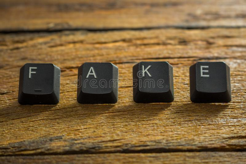 Word `Fake News` written with the keys of the computer keyboard on the wooden background royalty free stock image