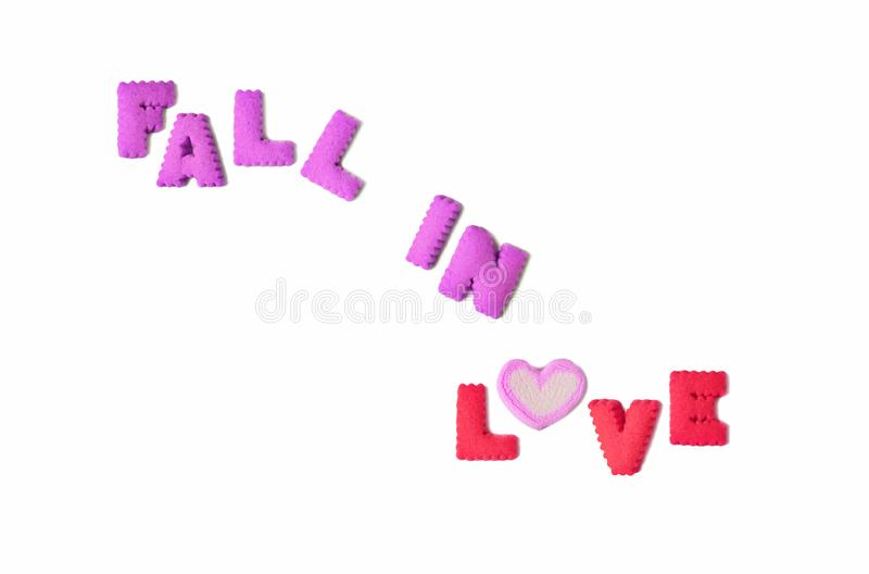 The word FALL IN LOVE spelled with purple and pink alphabet shaped biscuits and a heart shaped marshmallow candy. On white background, beautiful, card, chewy stock photography