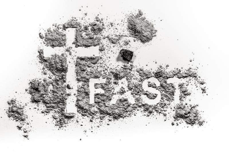 Word fast written in ash, dust or sand. And christian cross or crucifix symbol as lent fasting and abstinence concept royalty free stock photo