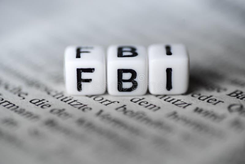 Word FBI door houten alfabetblokken wordt gevormd op krant die stock foto