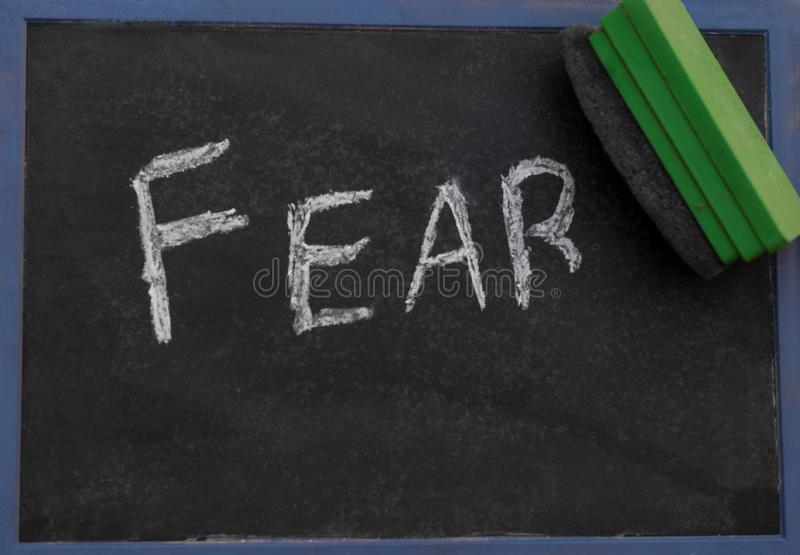 The word FEAR being erased from a chalkboard.  stock images