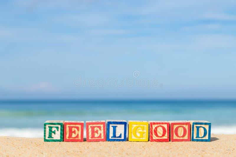 Word FEELGOOD dans les blocs colorés d'alphabet sur la plage tropicale photos libres de droits