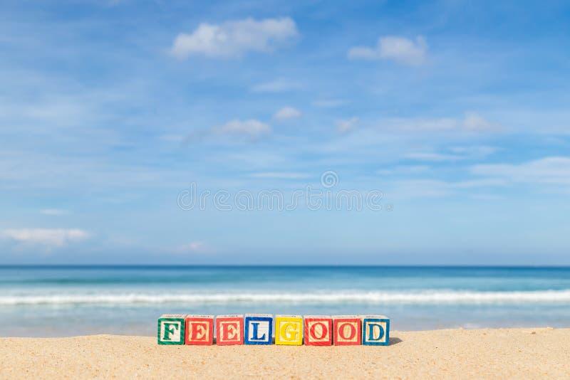 Word FEELGOOD dans les blocs colorés d'alphabet sur la plage tropicale photographie stock libre de droits