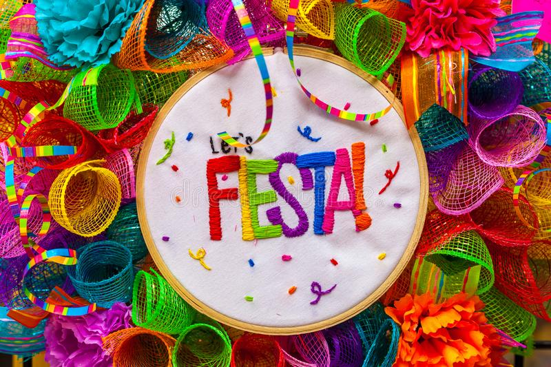 The word `fiesta` stitched in colorful letters on multicolored mash decorated with glitter and paper flowers. Decoration for San Antonio Fiesta Festival royalty free stock photo