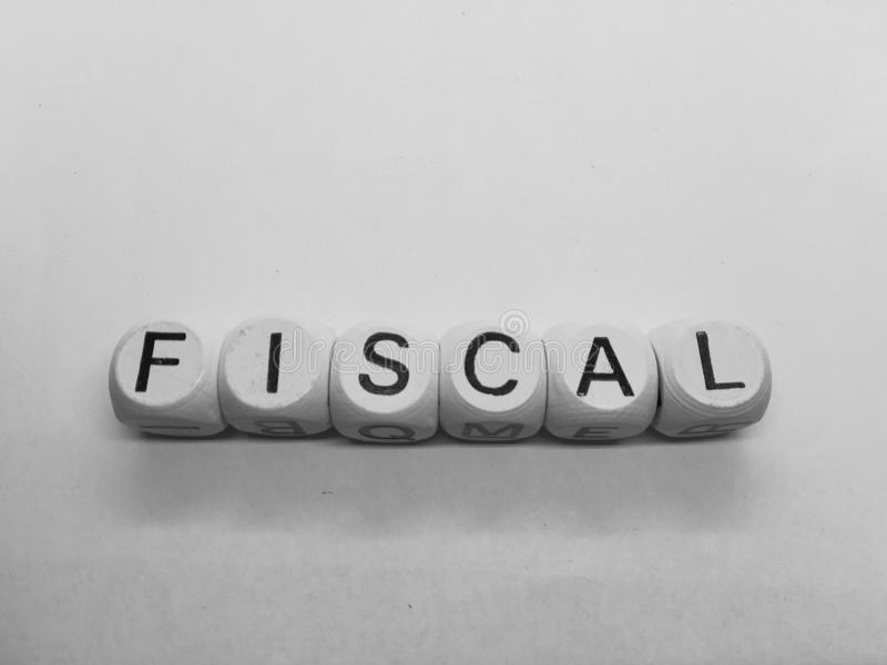 Word fiscal spelled in dice. Spelling of word fiscal using wooden dice on white background stock photo