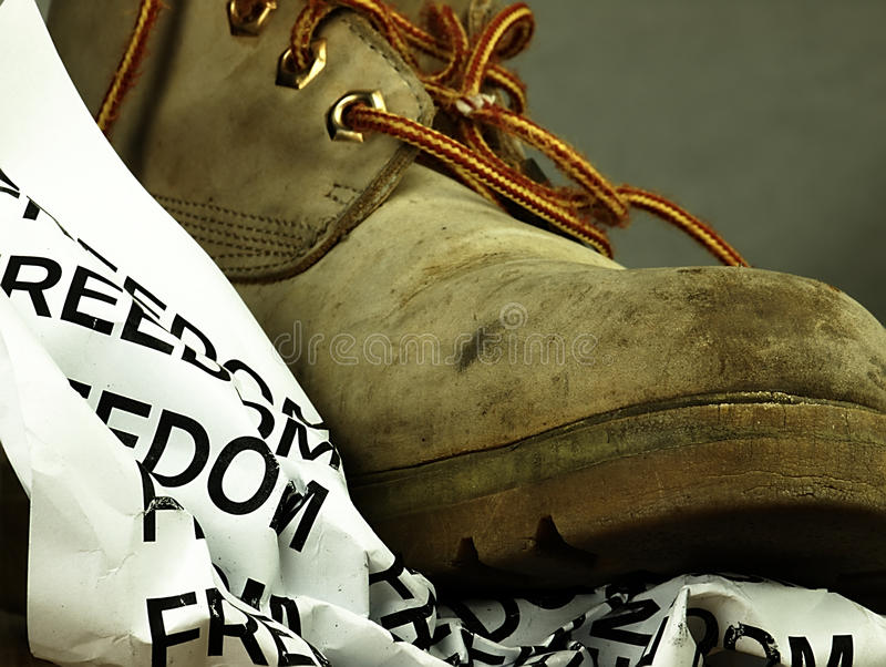 The word freedom crushed by a heavy, old military boot. Crumpled piece of paper with word freedom under the old, dirty and heavy military boot royalty free stock photo