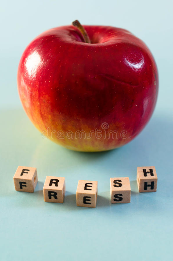 The word fresh written in cubes and an apple stock images