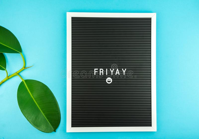 The word FRIDAY on a letter board with happy smiley emoji. Against blue background stock images