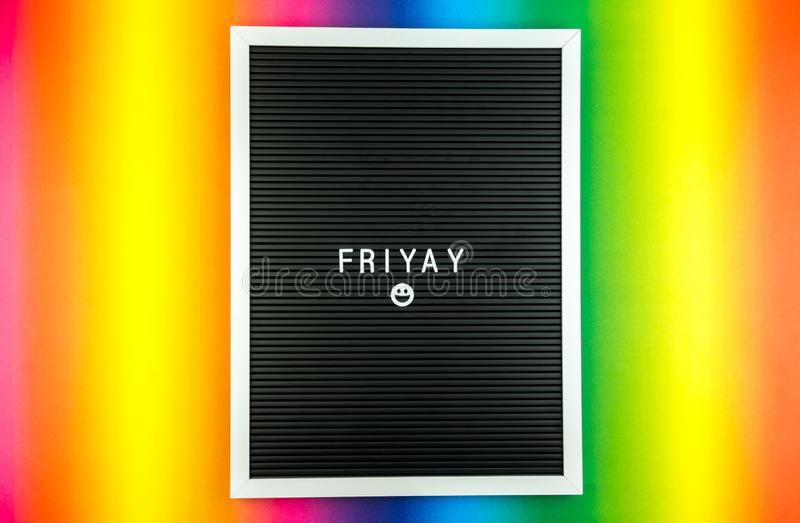 The word FRIDAY on a letter board with happy smiley emoji against multicolor background. The word FRIDAY on a letter board with happy smiley emoji against stock photography