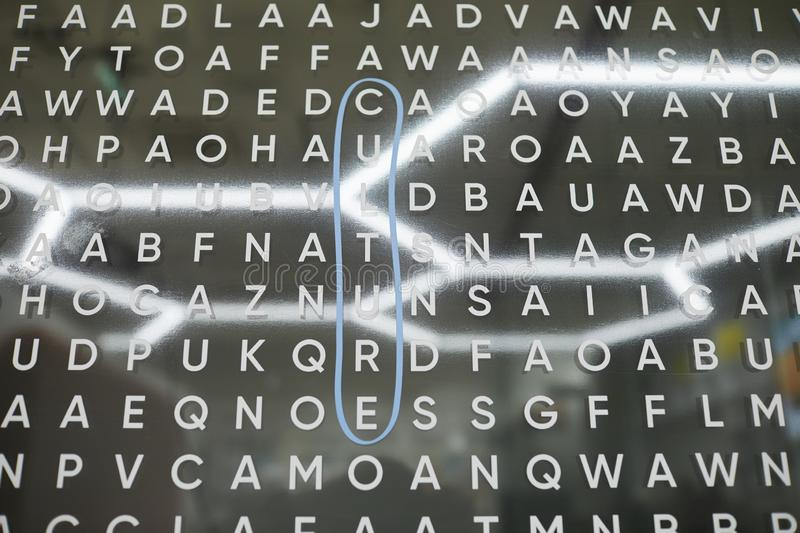Word game. Close-up of board with English letters and chandelier in shape of honeycomb reflected on it, word game concept royalty free stock photo
