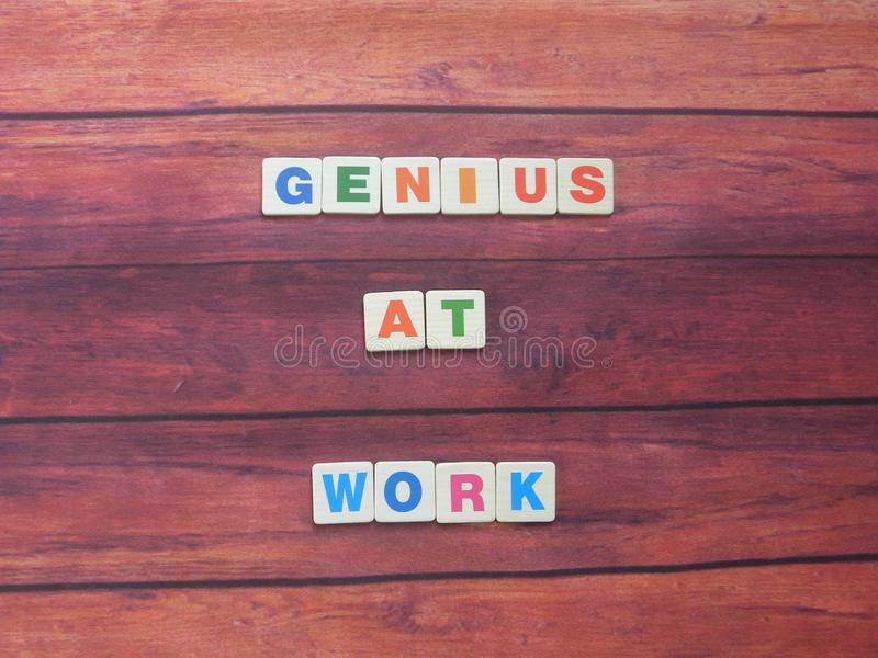 Genius at work. Word Genius at work on wood background stock photo