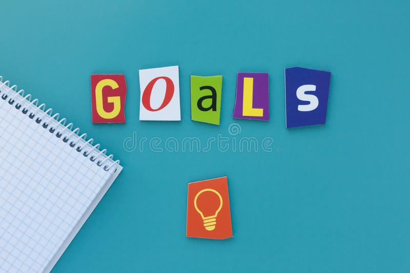 Word goals on blue background. Inscription goals of carved letters from the newspaper. A word writing text showing concept of goal stock images