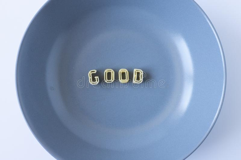 The word `good` made with pasta letters. The word `good` composed with real pasta letters in a blue dish royalty free stock photos