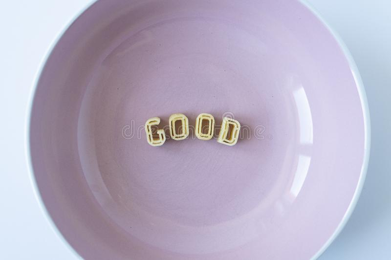 The word `good` made with pasta letters. The word `good` composed with real pasta letters in a pink dish royalty free stock image