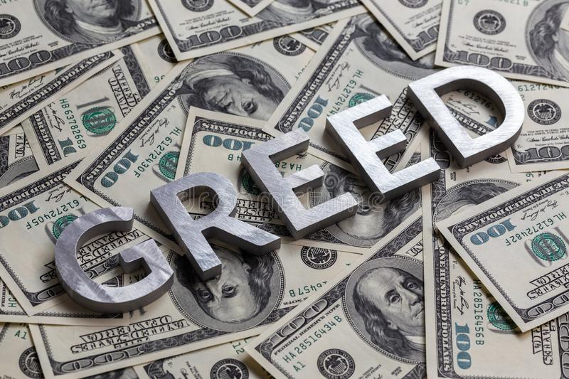The word GREED laid with aluminium letters on the US dollar banknotes background - with selective focus. And diagonal composition royalty free stock image