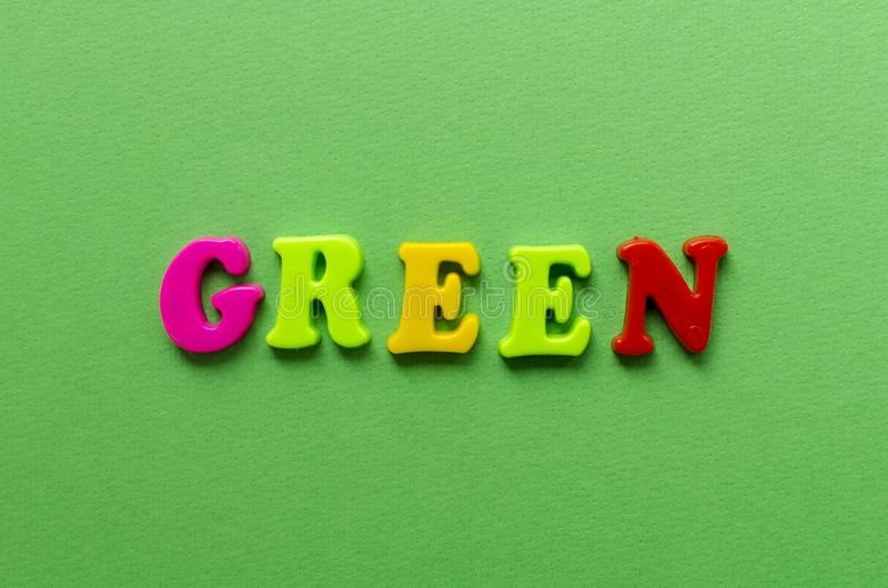 Word `green` from plastic colored magnet letters on green paper. Background royalty free stock photos