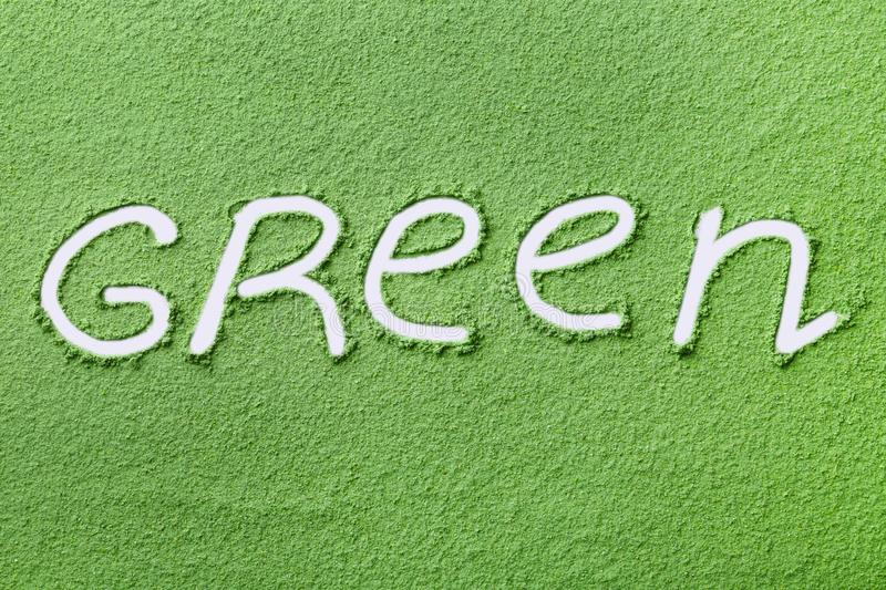 Word GREEN written on wheat grass powder. Top view stock photo