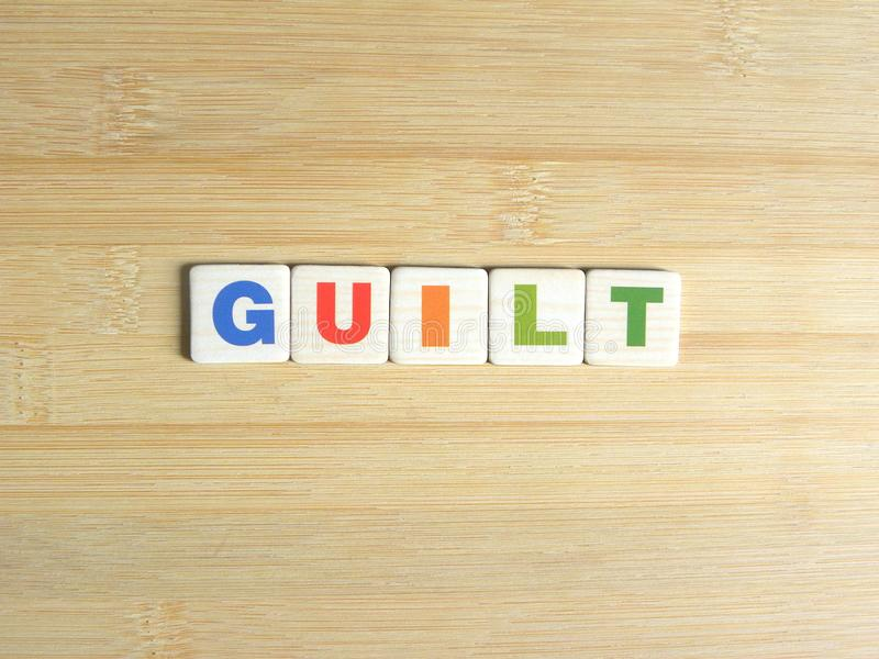 Word Guilt on wood background.  stock photo
