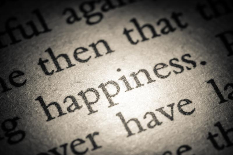 The word happiness on old page in a open book close-up macro. Vintage, grunge, old, retro style photo royalty free stock image