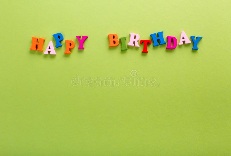 Word of happy birthday color wooden letters of the alphabet. Word of happy birthday of color wooden letters of the alphabet on a blue background stock photos