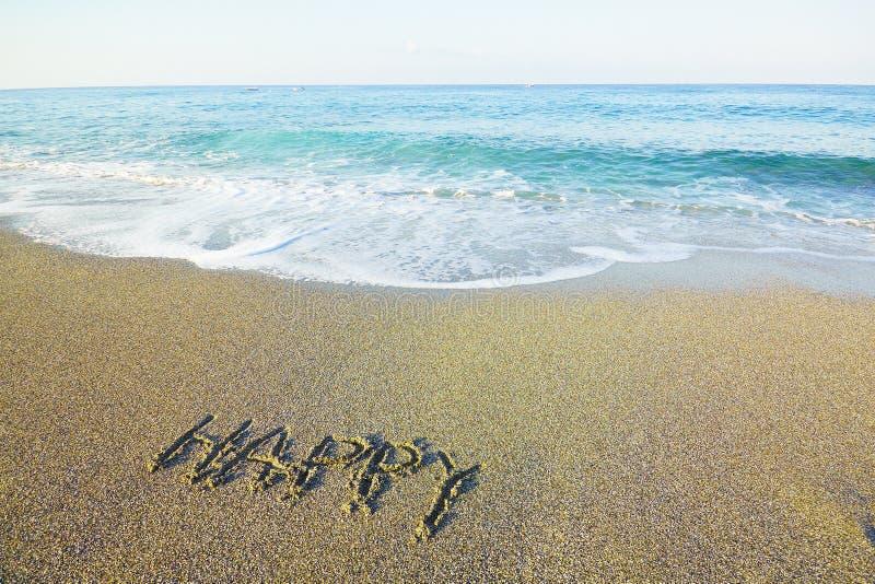 Word happy written on beach sand stock image