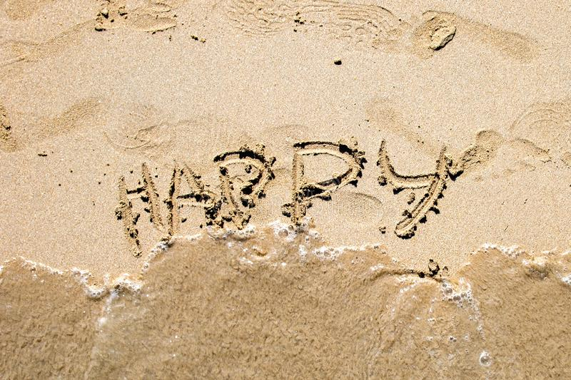 The word Happy is written with a finger in the sand. The inscription washes away the wave royalty free stock images