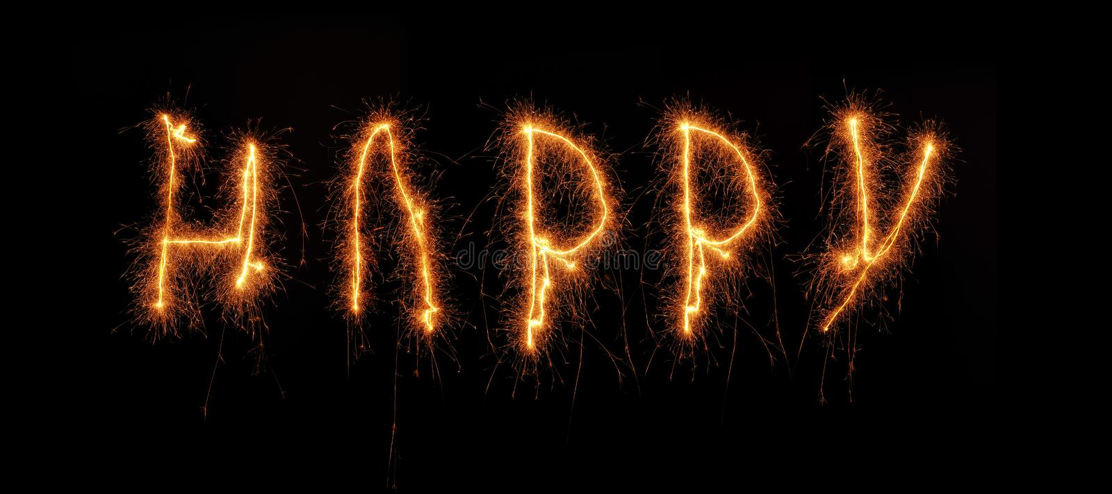 The word HAPPY written with a sparkler. On a black background stock image