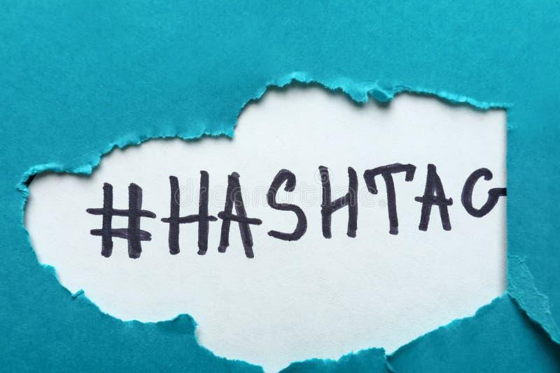 Word HASHTAG sous le papier déchiré de couleur photos libres de droits