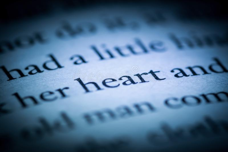 The word heart in a book close-up macro. Vintage, grunge, old, retro style photo. stock photos