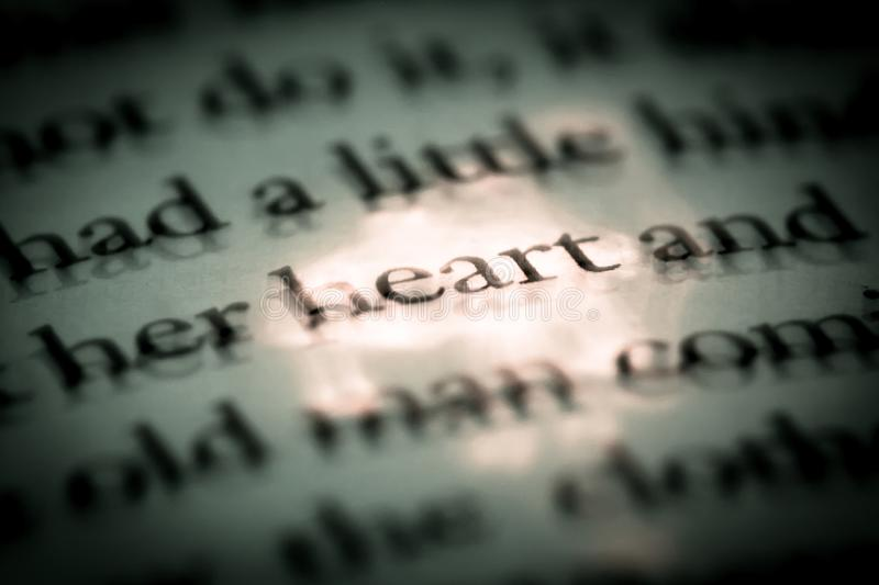 The word heart in a book close-up macro. Vintage, grunge, old, retro style photo royalty free stock image